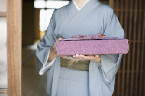 Woman in kimono holding gift, mid section