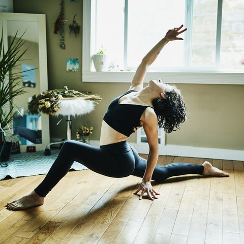 woman in low lunge with backbend pose while practicing yoga in bedroom of home