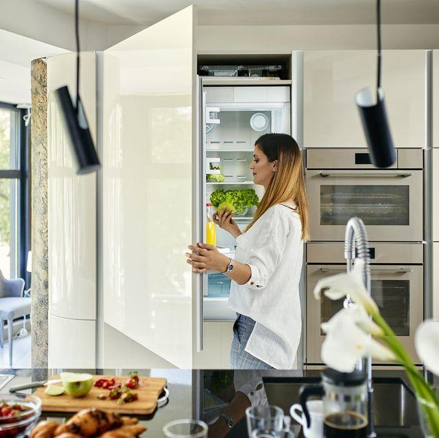 Woman in modern kitchen opening fridge