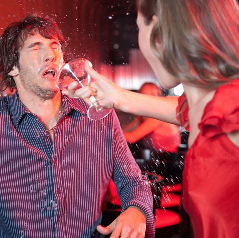 woman in nightclub throwing beverage in man's face