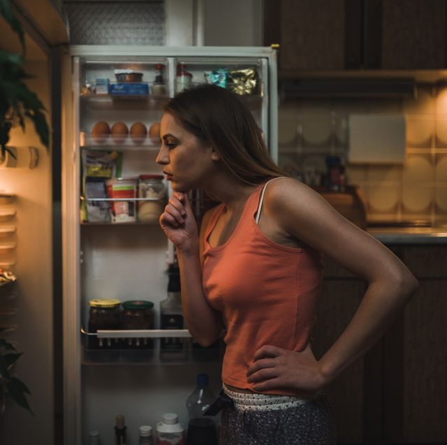 woman in pajamas in front of the refrigerator late night
