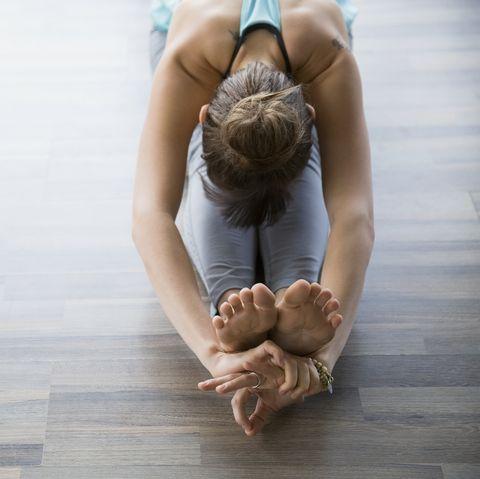 Woman in seated forward bend practicing mudra yoga