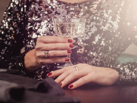 Woman in sequin new years eve dress drinking champagne sparkling wine