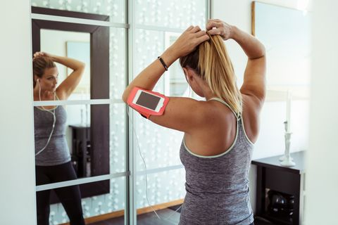 Woman in sport clothing tying ponytail while looking in mirror at home