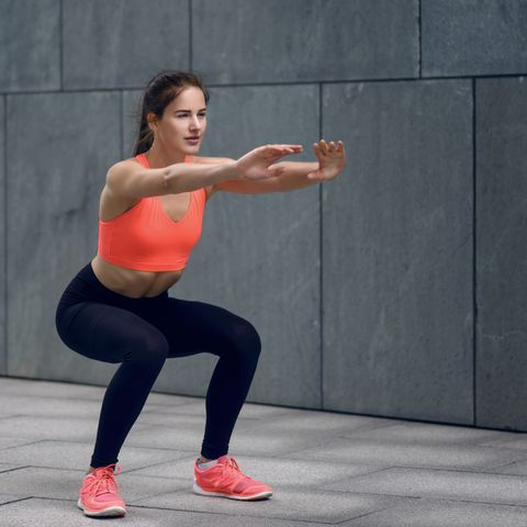 woman in sports clothing doing squats