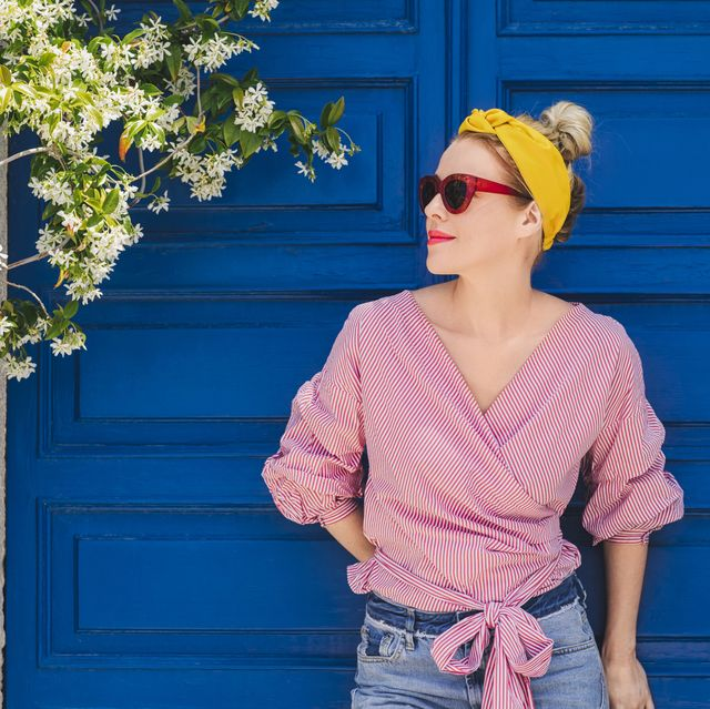 woman in sunglasses looking away while standing against door
