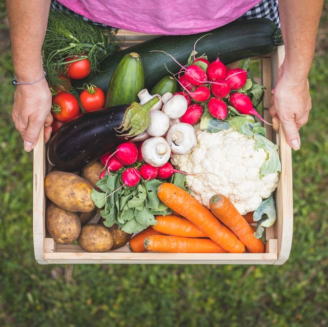 woman is holding wooden crate full of vegetables from organic garden