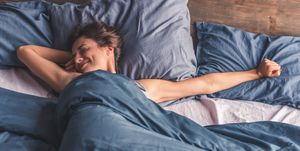 Woman is stretching and smiling while lying in bed in the morning