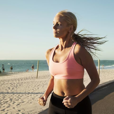 Woman jogging by the beach at sun set