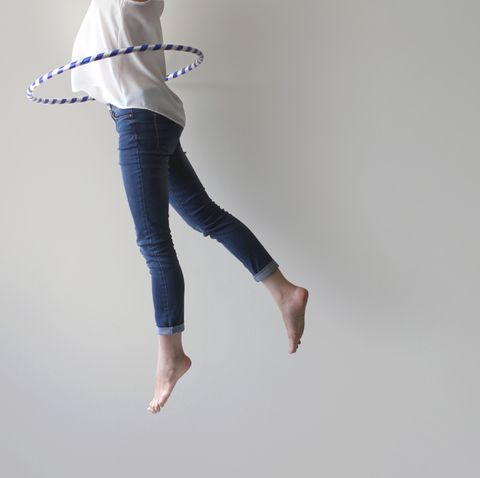 woman jumping mid air with plastic hoop round her waist