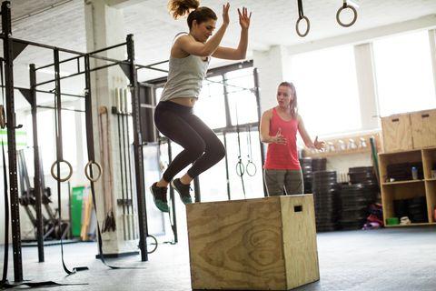 Mulher pulando na caixa com instrutor de fitness
