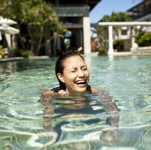 woman laughing and swimming at luxury resort