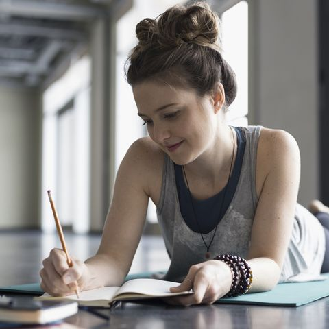 Woman laying on yoga mat writing in journal in gym studio