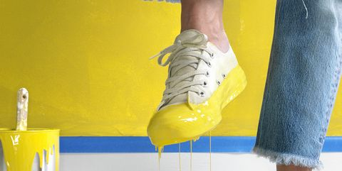 Woman lifting leg over yellow paint, low section