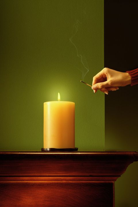 woman lighting candle with match