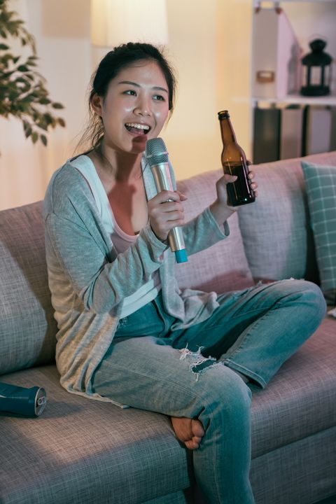 woman listening music singing drinking beer