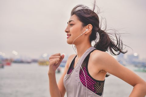 Woman Listening Music While Jogging By River Against Sky
