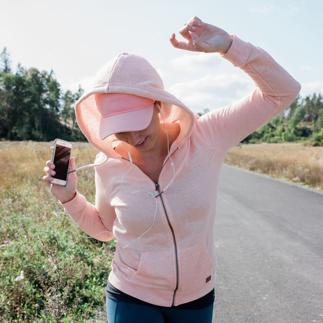 woman listening to music on her phone with headphones dancing outside