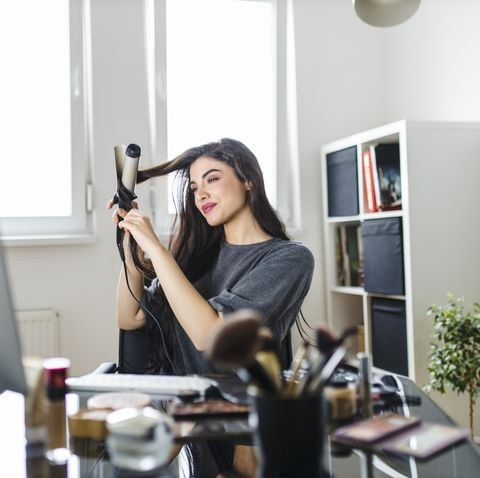 woman looking at computer and using her curling iron while sitting at the dressing table woman does her hair by watching a tutorial on the internet at the time of the corona virus pandemic