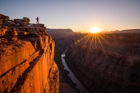 A Woman Looking at Grand Canyon and Colorado River from Toroweap Overlook at Sunrise