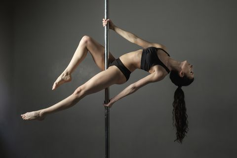 Woman looking away while exercising on pole against gray background