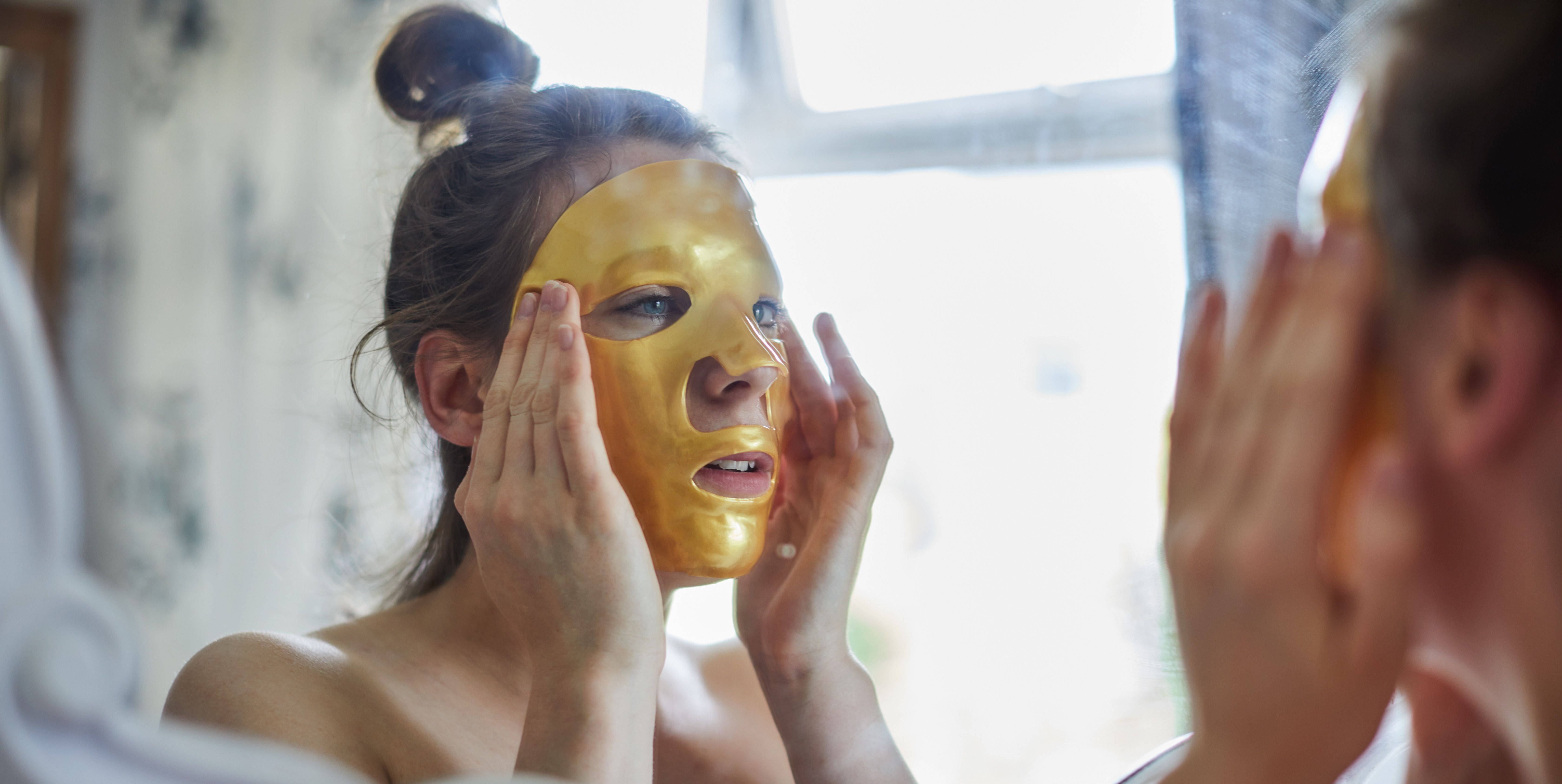 Woman looking in a mirror putting a face mask on