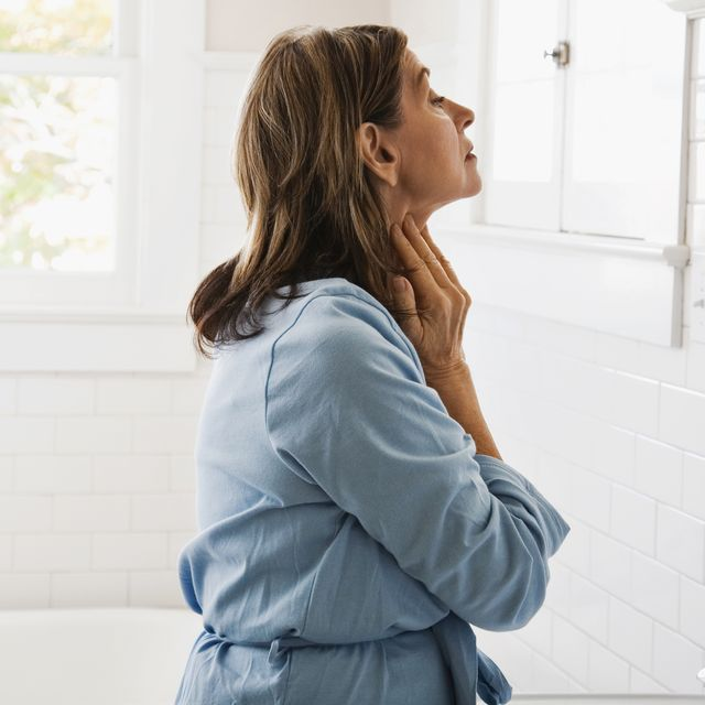 woman looking in bathroom mirror, touching neck