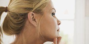 melanoma symptoms —woman giving herself a skin exam