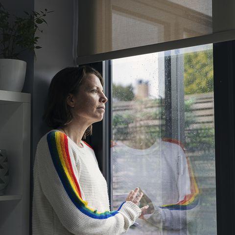 woman looking through window hopefully