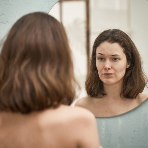 woman looks at her face in the mirror
