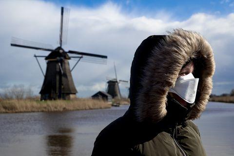 Vrouw met beschermend masker bij windmolens