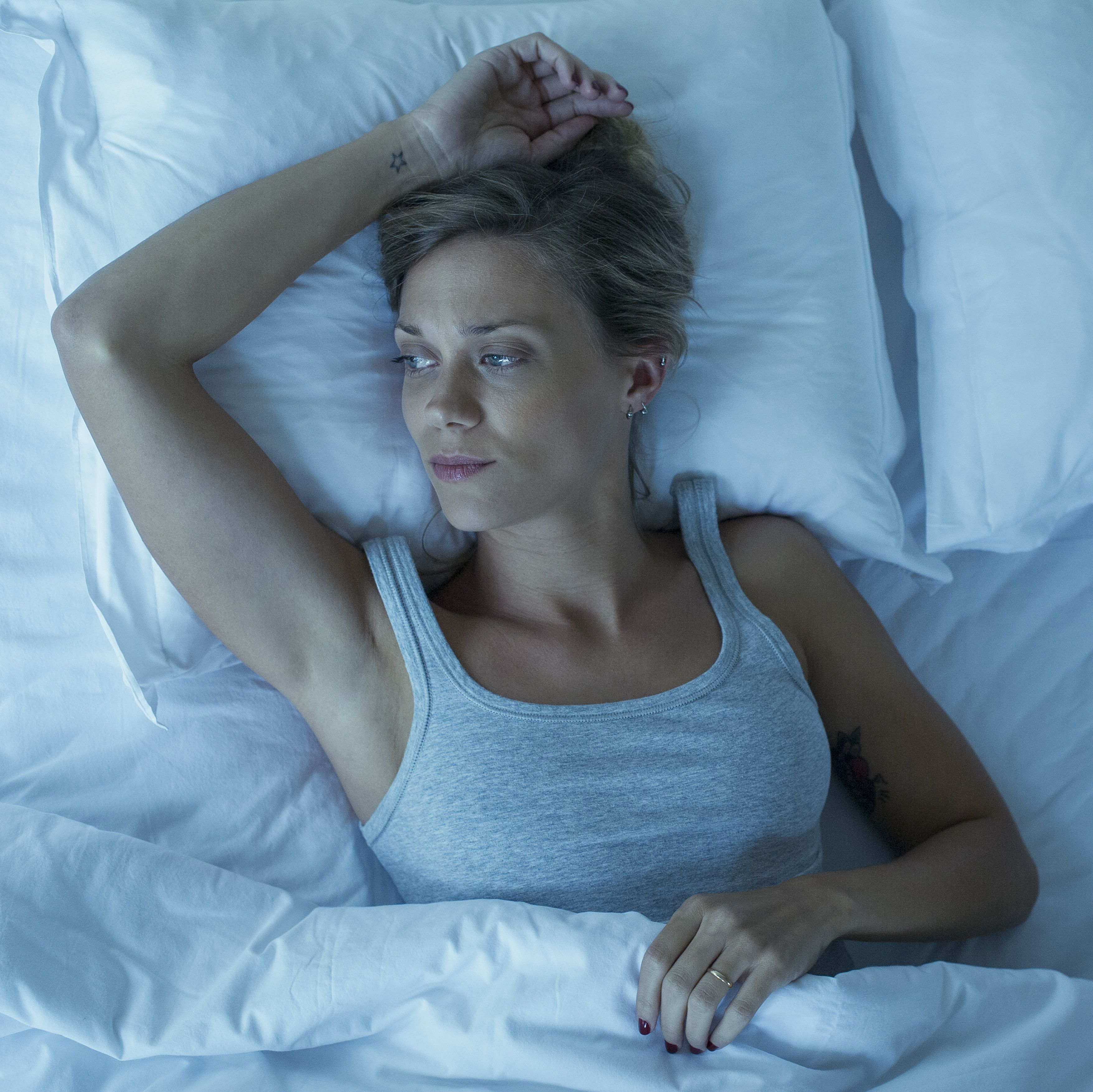 Woman lying alone in bed, looking away in thought