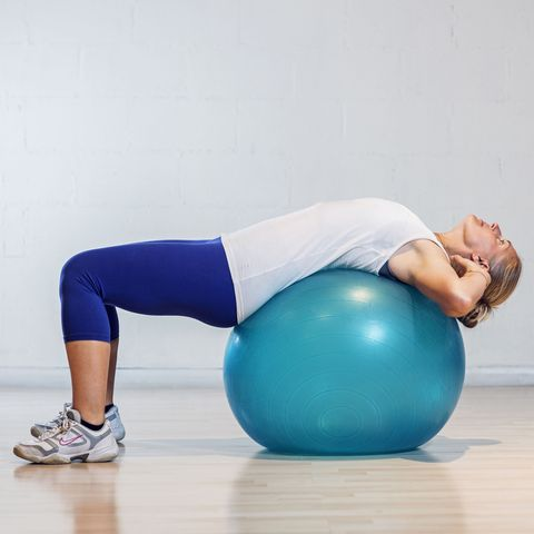 Woman lying down on a fitball