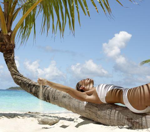 Mujer tumbada sobre una palmera.