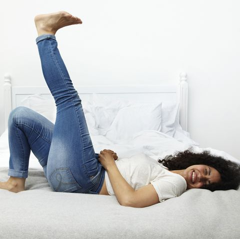 woman lying on bed laughing