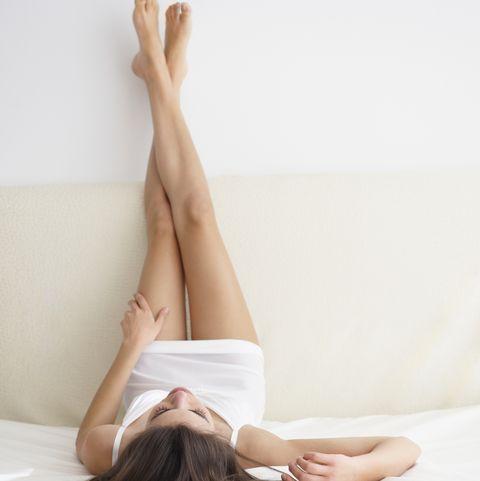 Woman Lying On Bed, Legs Resting On Headboard