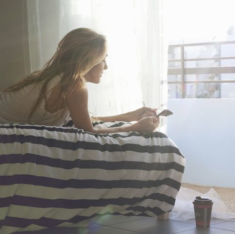 woman lying on bed with digital tablet and morning coffee