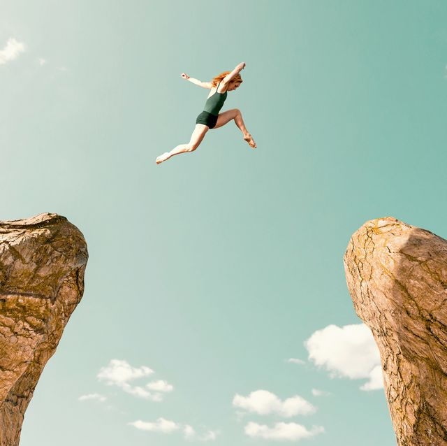 woman makes dangerous jump between two rock formations