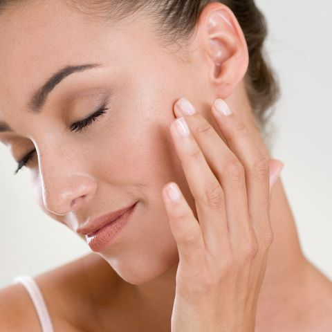 woman massaging her face with finger