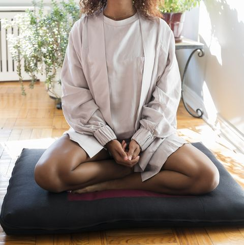 woman meditating on cushion