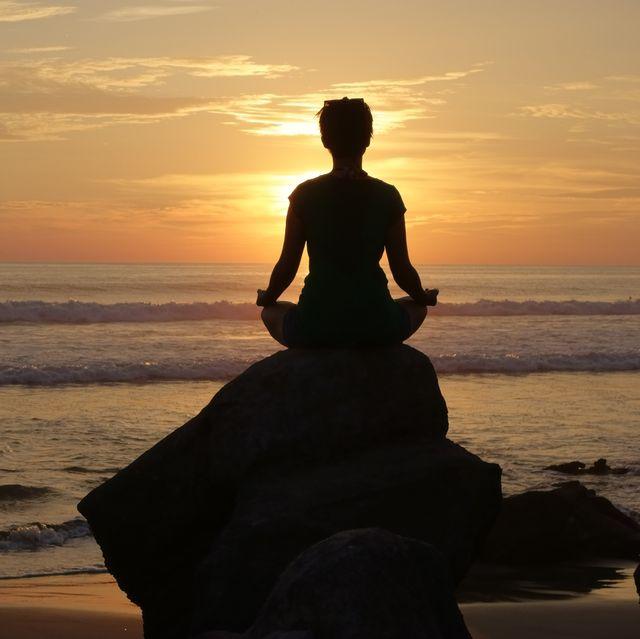 a woman meditation on an ocean side rock