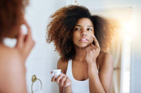 Woman using moisturizer in mirror