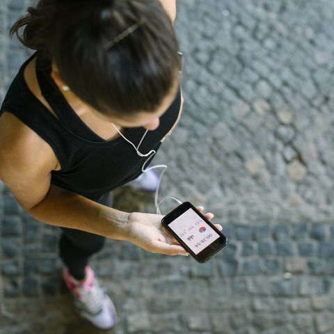woman monitoring her workout progress on fitness app