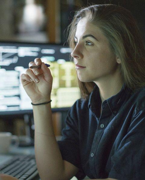 woman monitors dark office