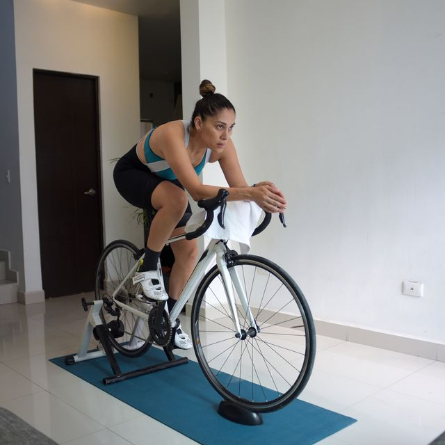 woman riding indoors on a bike trainer