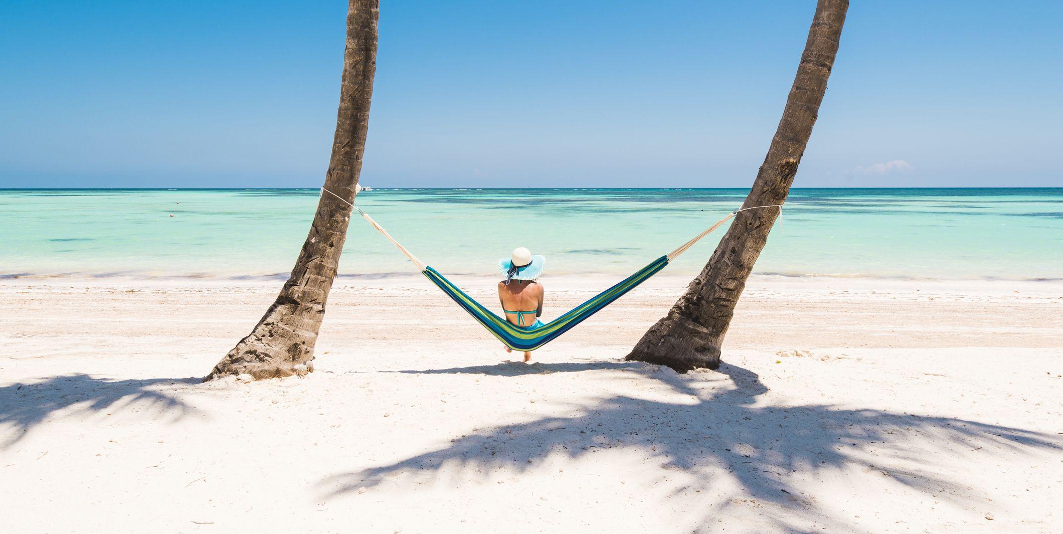 Caucasian woman lying on hammock on a tropical beach.