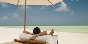 Woman on a sunlounger on a tropical beach.