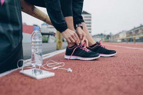 mujer atándose los cordones de sus zapatillas de deporte