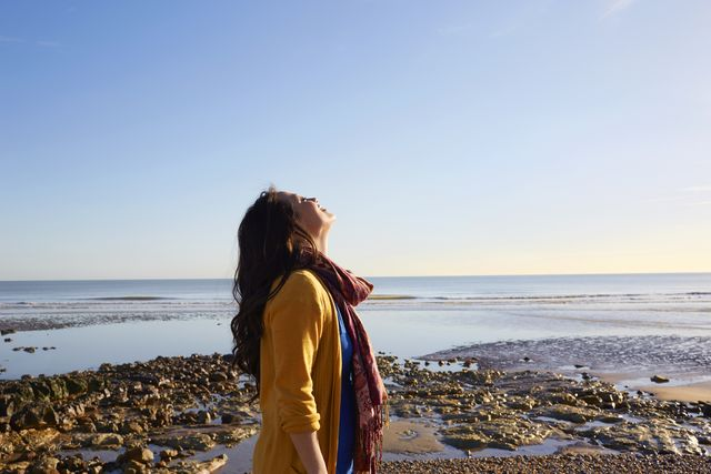 woman on the beach breathing in the fresh air