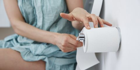 Woman on toilet reaching for toilet paper
